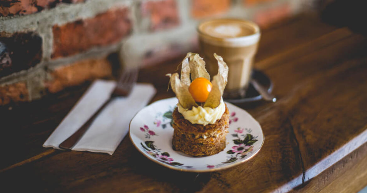 A close up of a cake on a plate with a coffee in the background