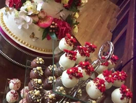 A close up of a wedding cake with truffles next to it